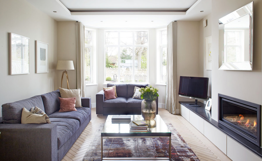 Grey sofas with pink cushions and herringbone parquet flooring