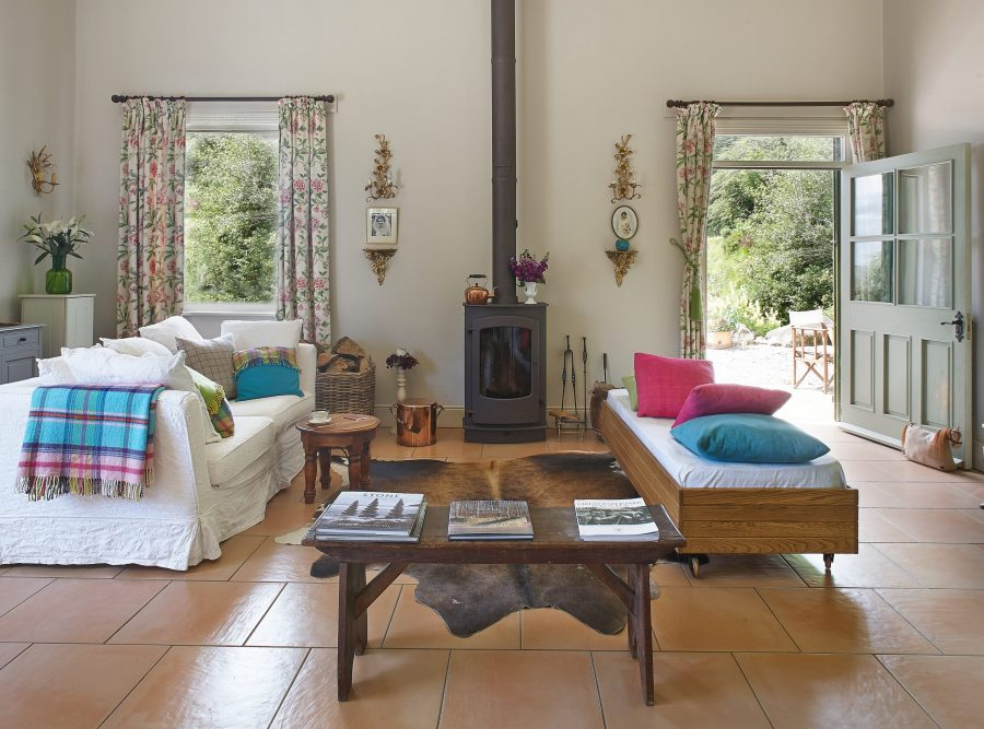 Converted stable with wood burning stove and sofa, tiled floor.