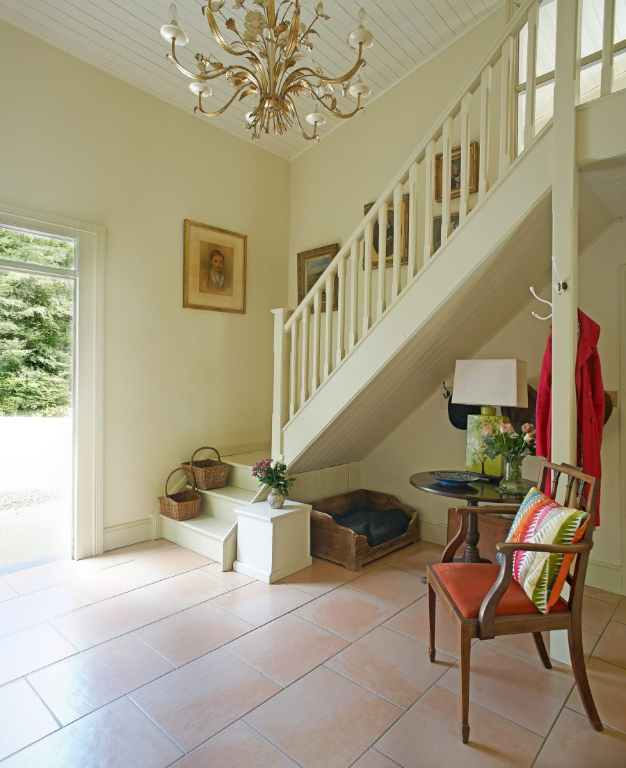 Double height entrance hall with stairs and chandelier