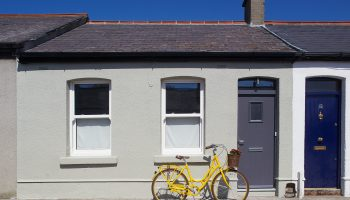 A yellow bike with a wicker basket with flowers in it on the front of the bicycle leaning against a cottage.