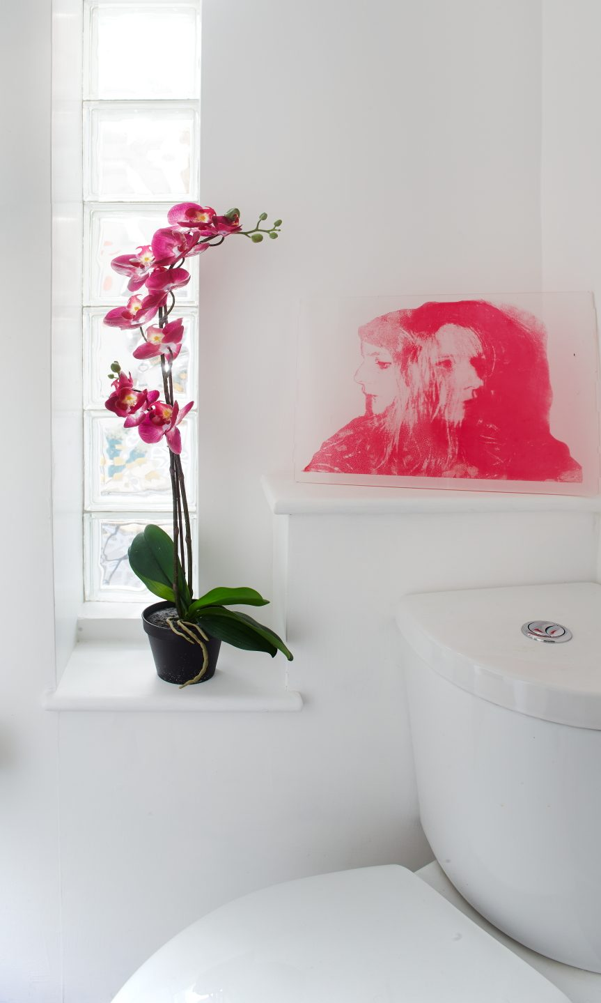 A toilet in a white bathroom with a dark pink orchid on the window sill and an art drawing