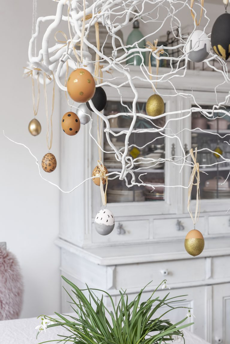 decorated easter eggs hanging on a tree branch