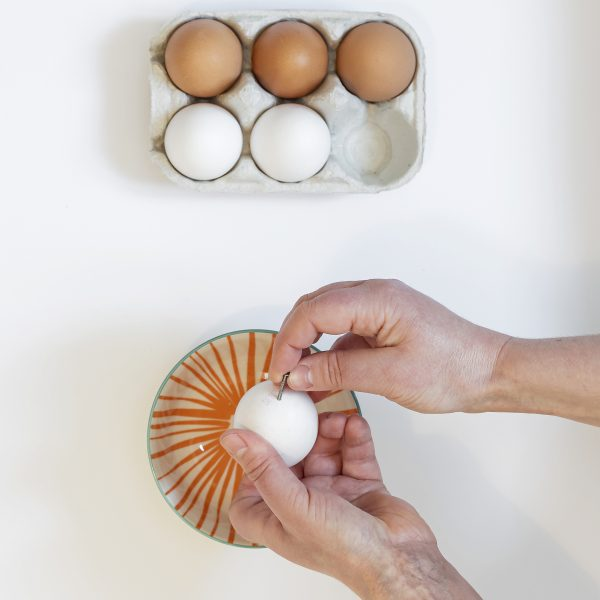 Making a hole in the egg by pushing a nail through it
